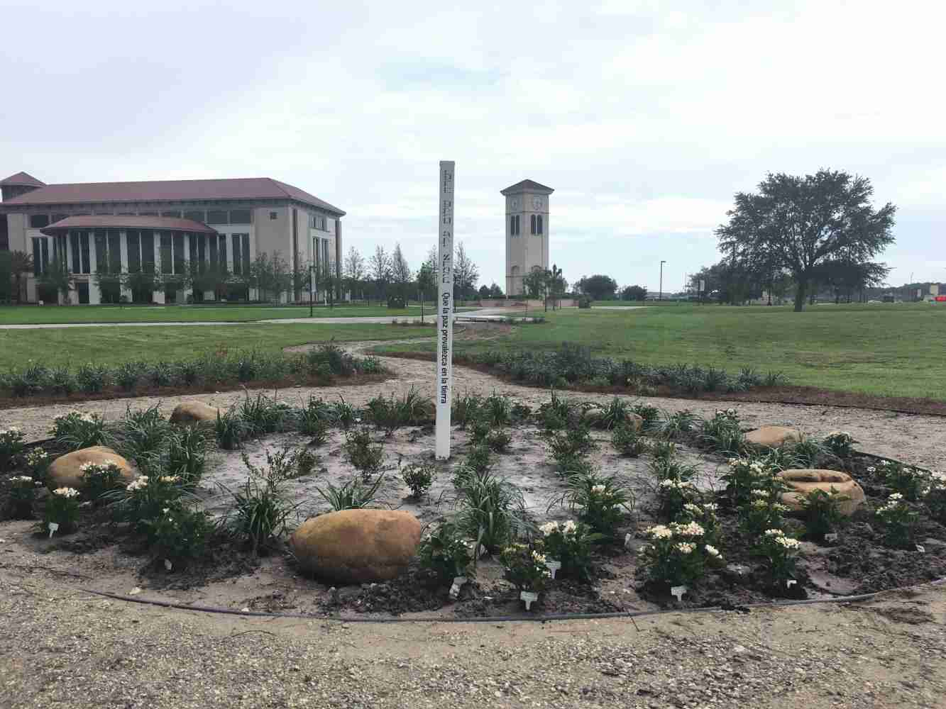 Osceola Campus Peace Pole and surrounded by 49 flowers.